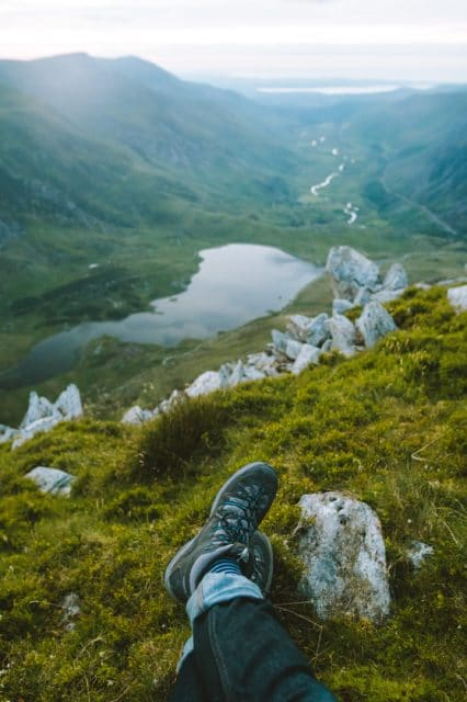 Hiker with hiking boots overlooking valley.